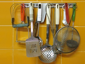 Various kitchen utensils on a kitchen hook strip. From left: – Pastry blender and potato masher – Spatula and (hidden) serving fork – Skimmer and chef